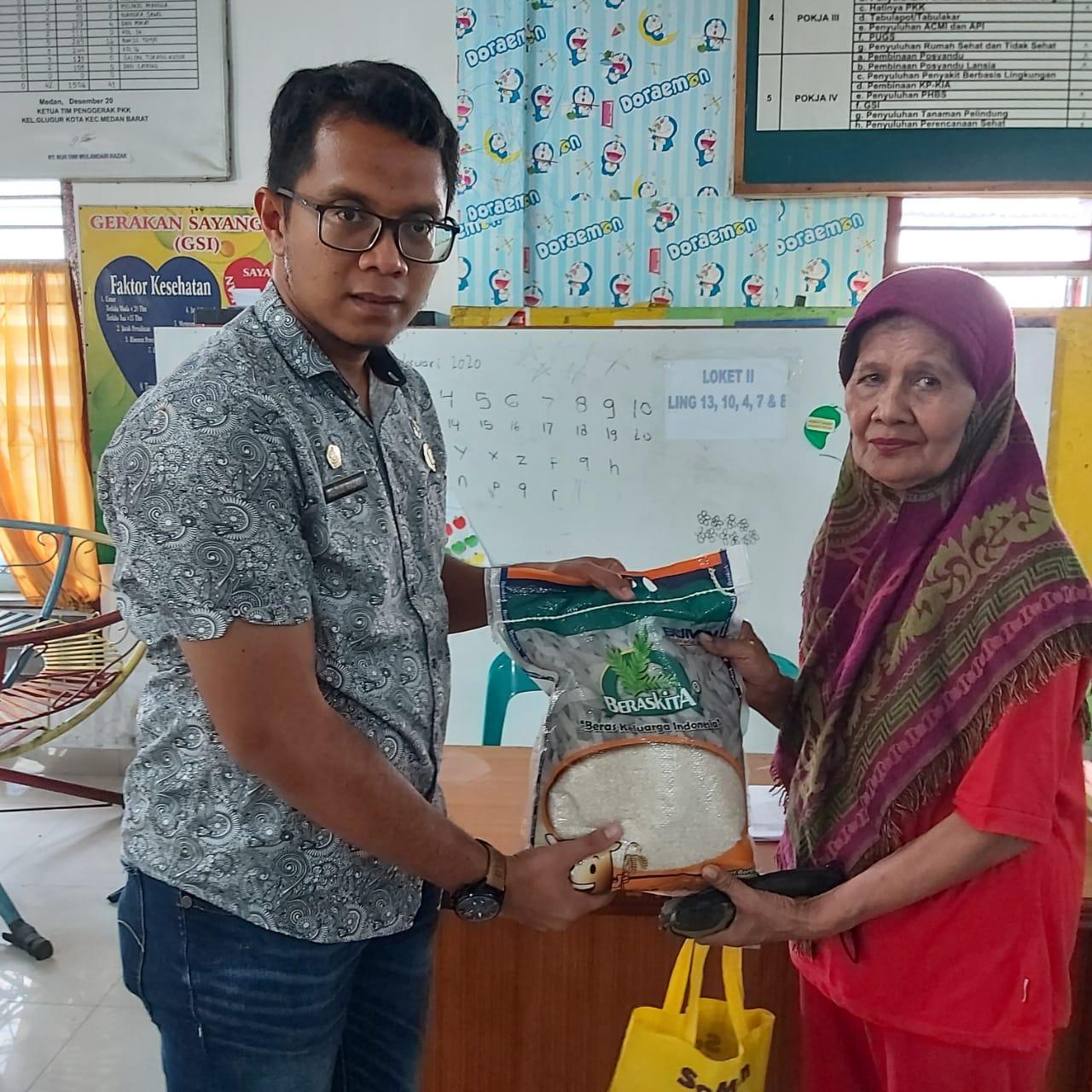 Ket. Foto : Lurah Kelurahan Glugur Kota, Abdul Razak SAB MSi menyerahkan bantuan beras dari Pemko Medan kepada warga di Aula Kelurahan Glugur Kota, Kamis (9/4/2020).(masrianto)