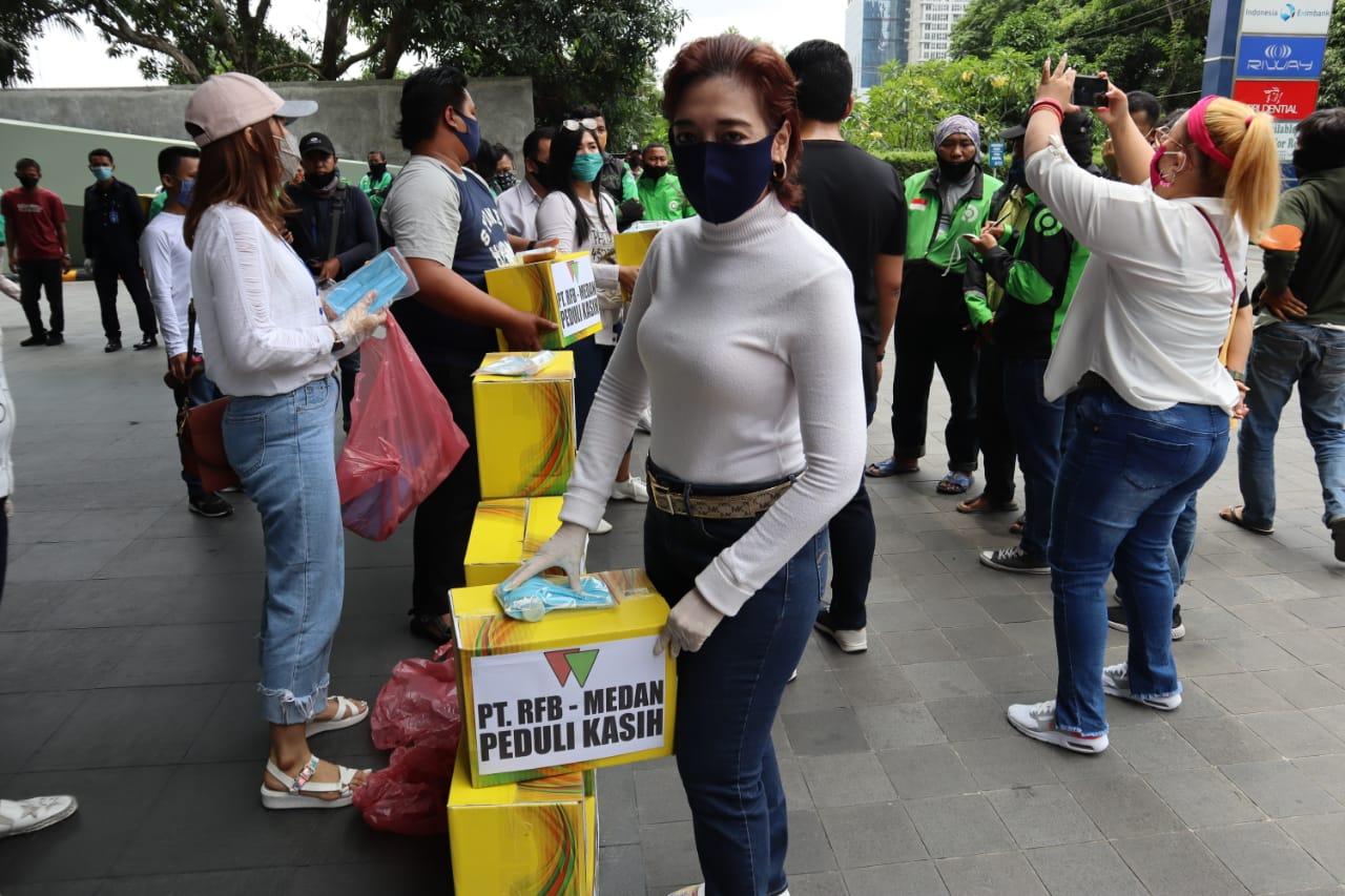 Ket Foto : Kepala Cabang PT PT Rifan Financindo Berjangka (RFB) Medan, Sonya Kadarmanik saat membagikan paket sembako kepada para driver ojek online di halaman kantornya. (Esal)