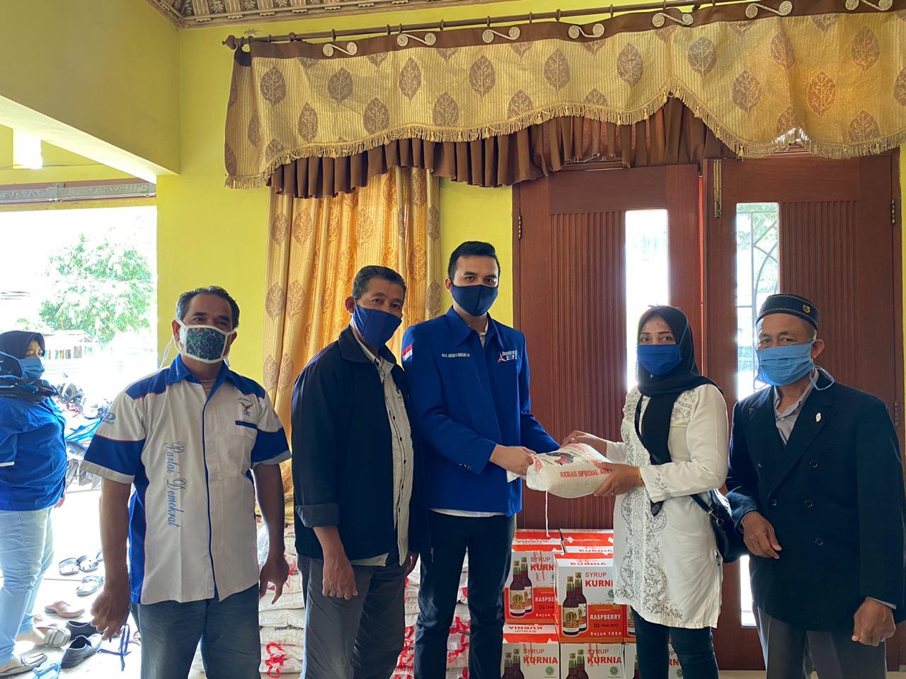 Ket foto : Anggota DPRD Medan, Ishaq Abrar Mustafa Tarigan,SP (tengah) ketika menyerahkan beras kepada perwakilan warga.(Esal)